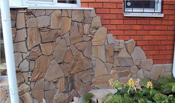 наклеювання природного каменю на стіну фасаду