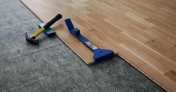 процес вкладання паркетної дошки на підлогу