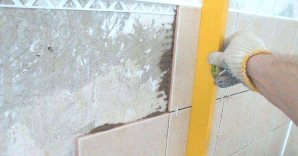 перевірка рівнем при вкладанні плитки на стіни