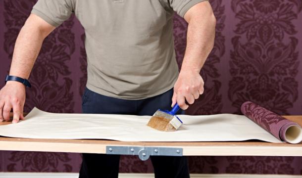 процес наклеювання підготованих вінілових шпалер на стіни
